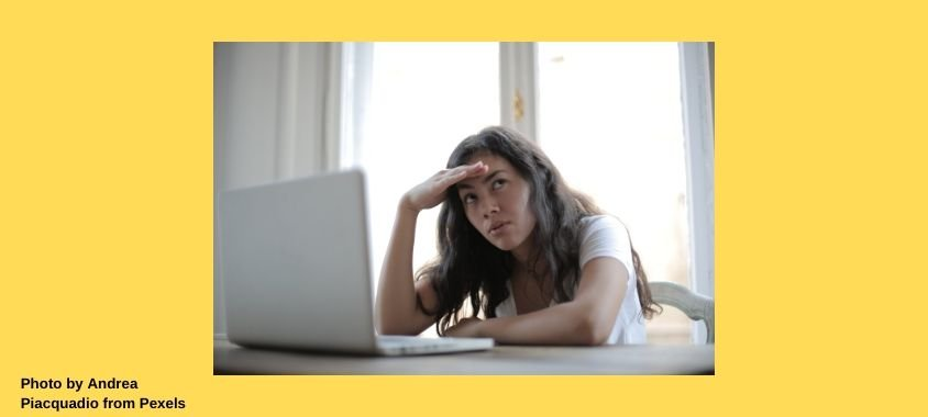 A woman working on a laptop looks annoyed